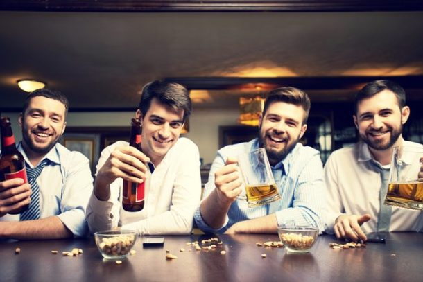 Four happy white collar workers toasting with beer standing at bar counter